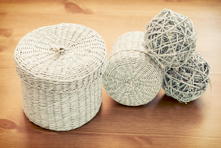 set of white seagrass basket on a wooden table.